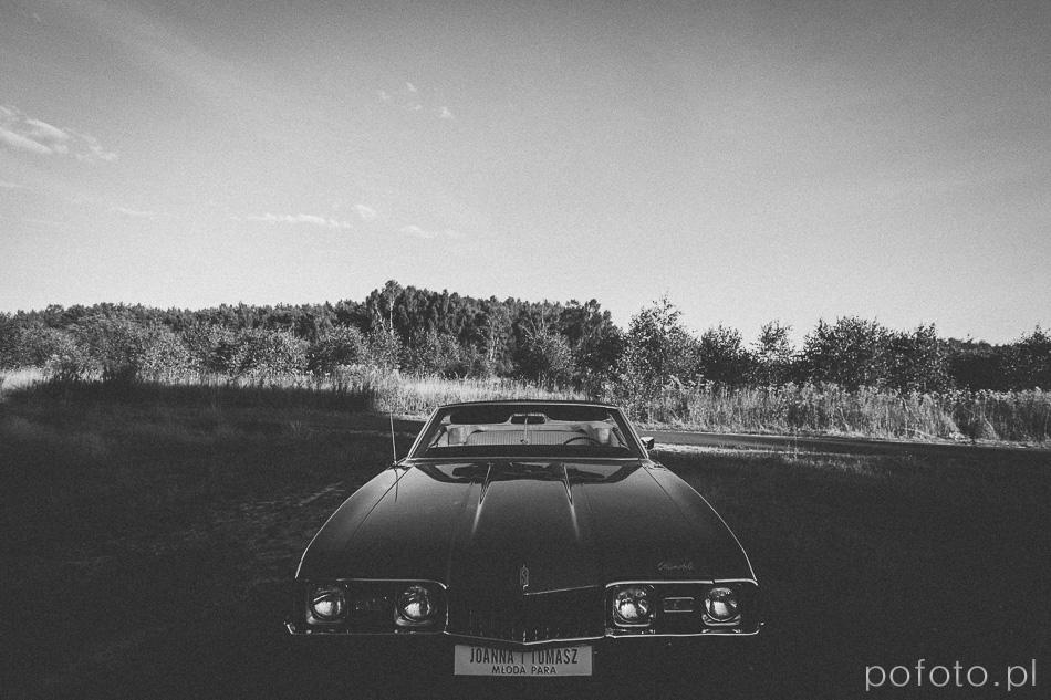 czarno białe zdjęcie opuszczonego Oldsmobila na polanie