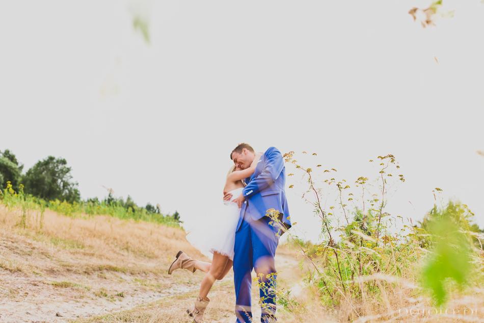 radosne zdjęcie plenerowe młodej pary, ona wiesza się na szyji męża