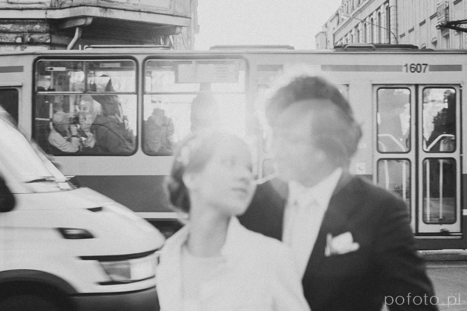 czarno białe zdjęcie młodej pary poza głębią ostrości, w tle zgiełk miasta