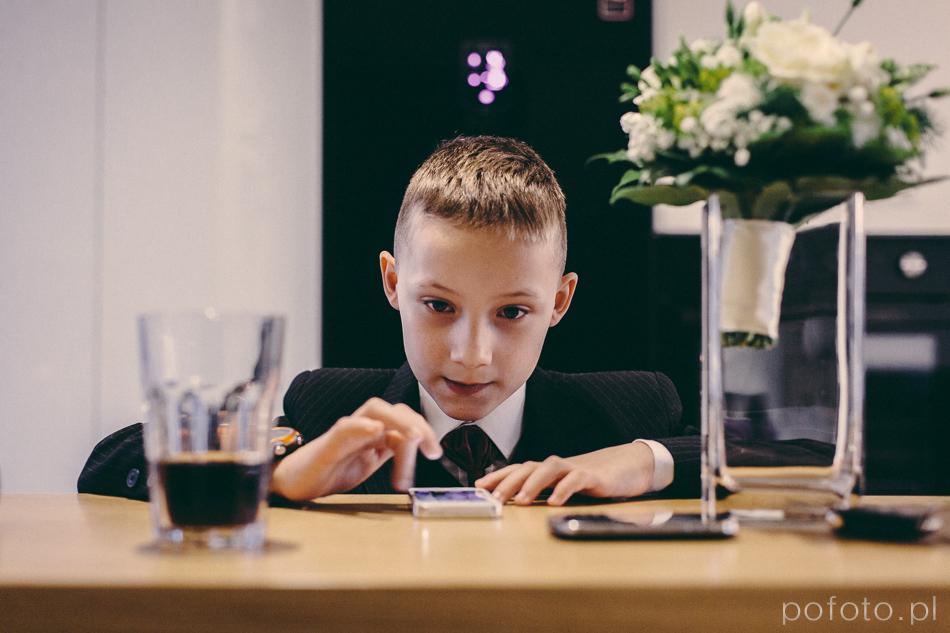 chłopiec bawi się telefonem, w kadrze wiązanka ślubna w wazonie