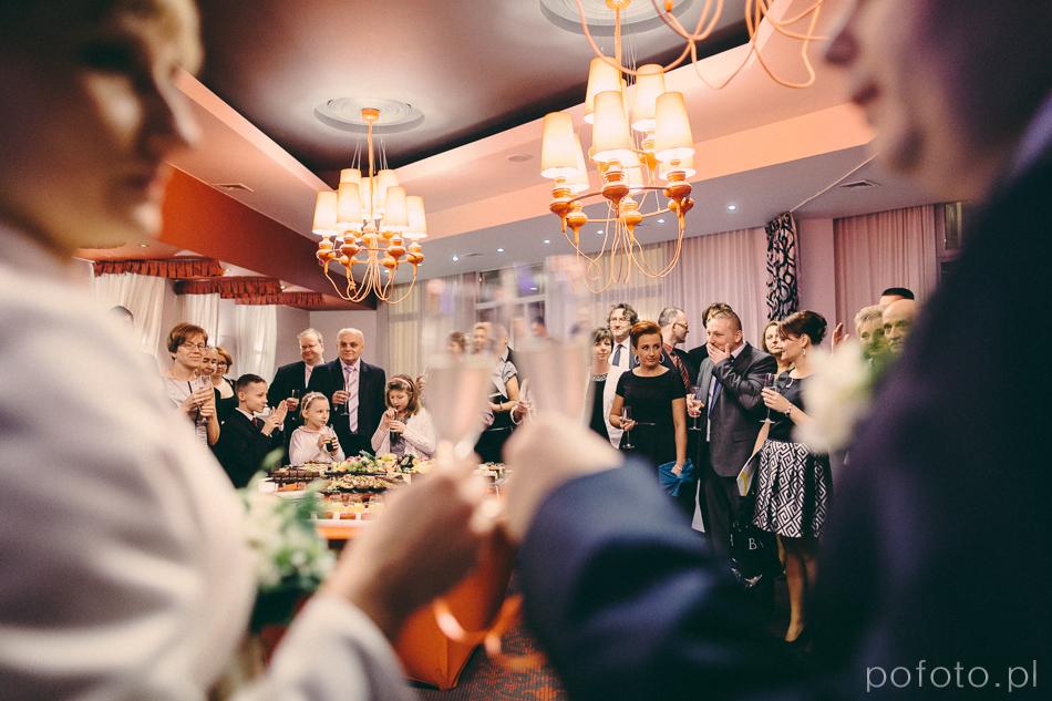 powitanie w sali restauracyjnej nobo hotelu para z szampanem przed głębią ostrości