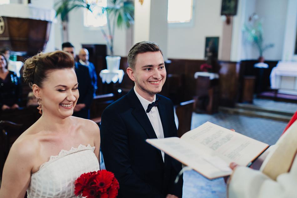 reportaż ślubny Kasi i grześka - uśmiechnięta para młoda w kościele podczs ceremonii