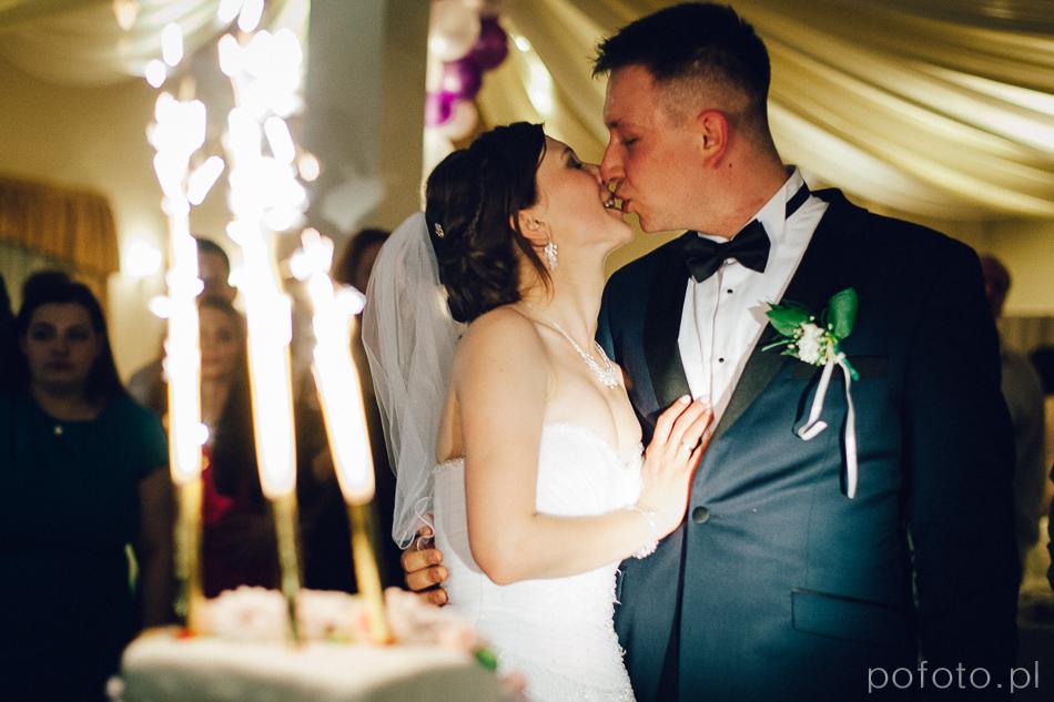 pocałunek pary młodej przy torcie podczas wesela w kołobrzegu - fotoreportaż ślubny