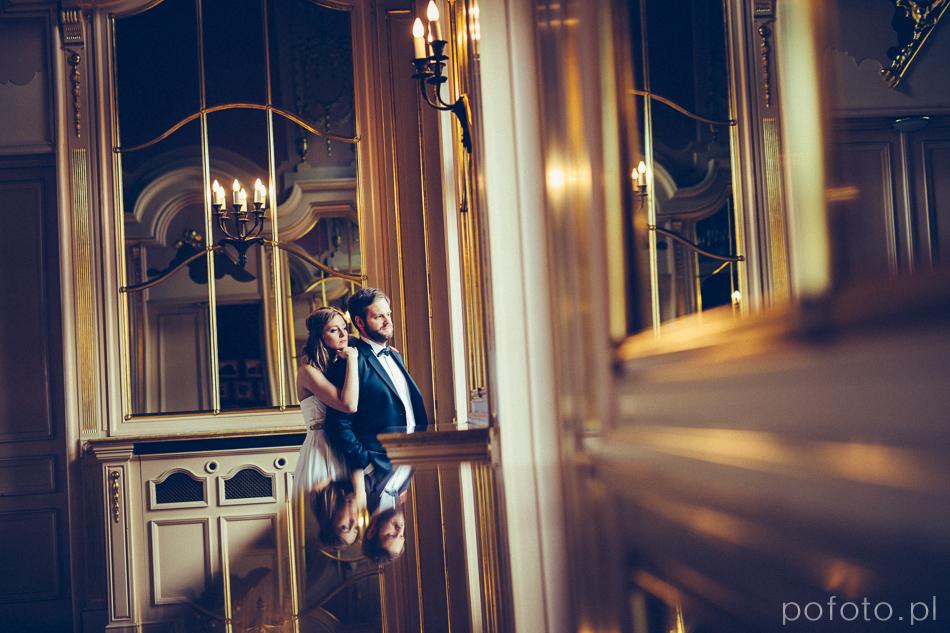 para młoda wygląda przez okno w Pałacu Poznańskiego podczas plener ślubny